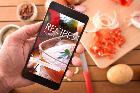 Foto de Smartphone with online recipes app and ingredients background. Use of the digital devices to cook. Horizontal composition. Top view - Imagen libre de derechos
