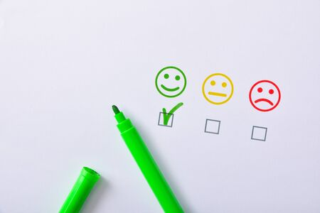 Foto de Positive satisfaction marked with green marker pen represented with colored emoticons on white paper. Horizontal composition. Top view. - Imagen libre de derechos