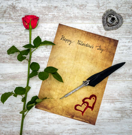 Photo pour Antique preachment with hand written Happy Valentine's Day, red rose, red painted 2 harts, detailed silver quill stand in shape of hart accented by flat lying beautifully ornamented silver and black quill on rustic white painted oak - image libre de droit