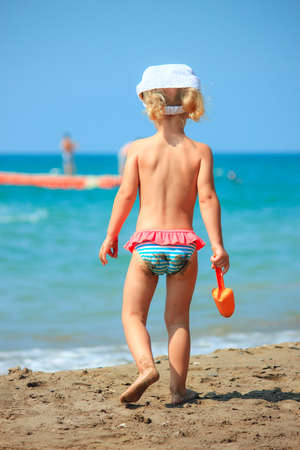 Photo pour  One little girl walk on the beach with spades. Bright summer time. - image libre de droit