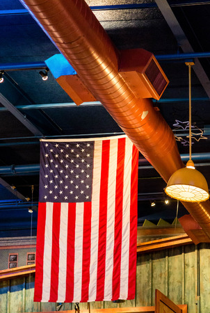 An American flag hanging from ceiling with copper ductwork