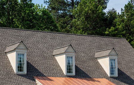 Photo pour Three white wood dormers on an old grey shingle roof - image libre de droit
