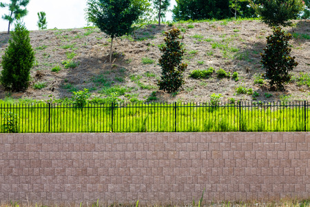 Photo pour A Block Retaining Wall Topped with Black Iron Fence on a landscaped hill - image libre de droit