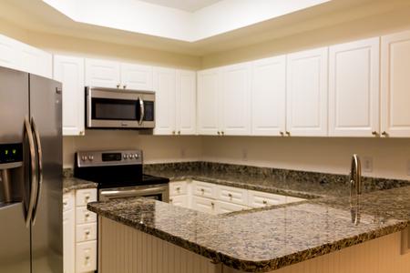Foto de New stainless steel appliances and granite countertops with white wod cabinets - Imagen libre de derechos