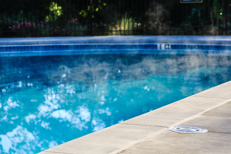 Photo pour Steam Rising from Heated Swimming Pool with Concrete Deck - image libre de droit