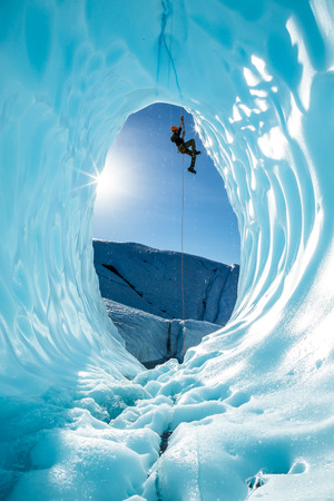 Photo pour Hanging from a rope fixed above the entrance of a large blue ice cave, an ice climber ascends out of the glacial cavern. The scene is from the Matanuska Glacier, in the wilderness of Alaska. - image libre de droit