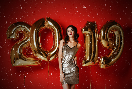 Photo for Cheerful happy beautiful young woman is smiling on party With Gold 2019 Balloons. Party, holiday, christmas concept. confetti. Model in shiny sequin dress laughing around confetti, snow and balloons. - Royalty Free Image