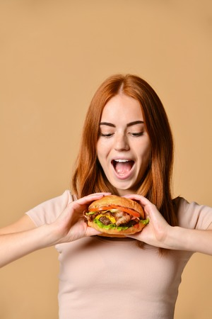 Photo for Funny crazy smiling Skinny ginger girl in beige t-shirt eating holding hamburger, looking away - Royalty Free Image