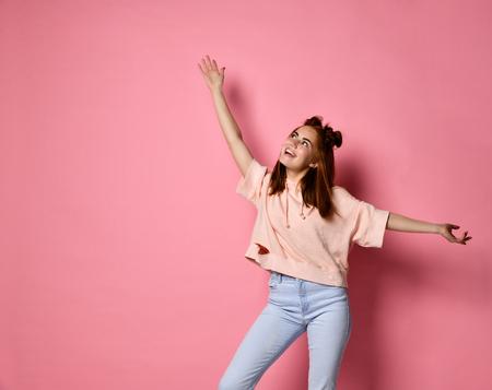 Foto de Portrait of a cheerful young red-haired teenager girl joyfully looking up Woman raising arms above her head - Imagen libre de derechos