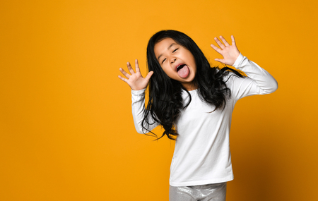 Foto per funny cute little asian girl shows the tongue over yellow wall background - Immagine Royalty Free