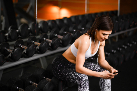 Foto per Sports girl resting after a hard training session in gym, sitting near the rack with dumbbells, listening to music from a mobile phone. - Immagine Royalty Free