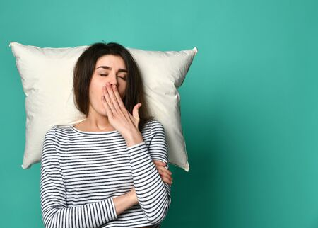Photo pour sleeping woman of the 20s on pillow in home clothes, happily relaxing at home and yawning because of insomnia isolated on a light background. - image libre de droit