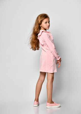 Photo pour Beautiful little girl with long blond hair and blue eyes, standing on a white background, wearing a pink casual dress and gym shoes, teenager style. Sale, holidays, birthday party concept. - image libre de droit