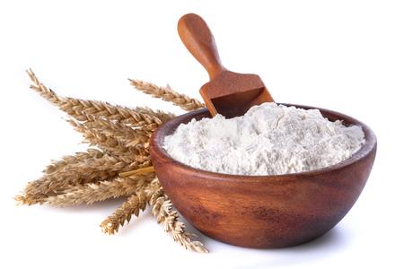 Foto de flour with wheat in a wooden bowl and shovel on a white background - Imagen libre de derechos