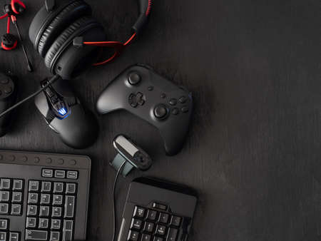Foto de gamer work space concept, top view a gaming gear, mouse, keyboard, joystick, headset, mobile joystick, in ear headphone and mouse pad on black table background. - Imagen libre de derechos