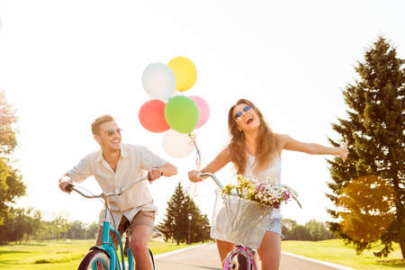 Photo for couple in love on bikes with balloons and flowers - Royalty Free Image