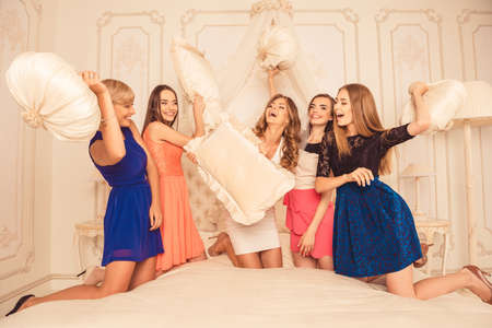 Photo pour girls celebrate a bachelorette party of bride. bridesmaids fighting pillows - image libre de droit