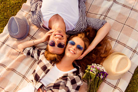 Photo pour top view of a couple in love lying on a picnic plaid - image libre de droit