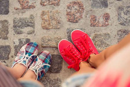 Photo for top view of a two pairs of sneakers shoes walking on paving ston - Royalty Free Image
