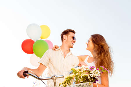 Photo pour couple in love on bikes with balloons and flowers - image libre de droit
