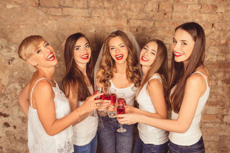 Photo pour Beautiful bride with happy bridesmaids celebrating hen-party with red champagne - image libre de droit