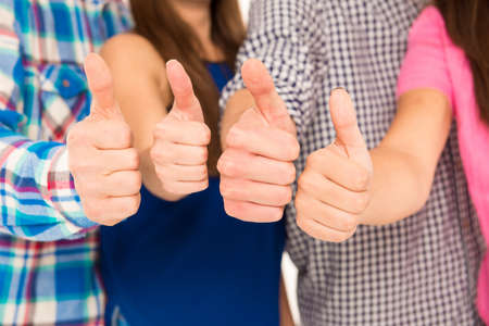 Photo pour Closeup photo of a group showing thumbs up - image libre de droit