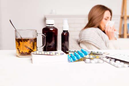 Foto de Sick woman, cup of tea, pills and mixture, close up photo - Imagen libre de derechos