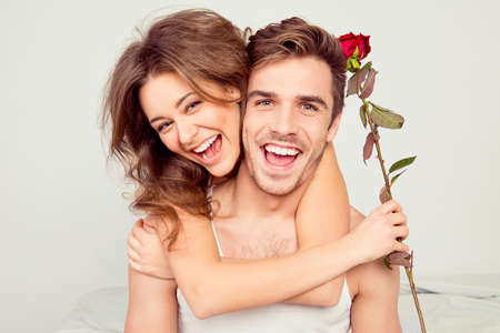 Photo pour Cheerful young couple in love embracing in the bedroom with rose - image libre de droit