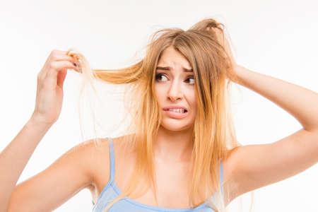 Foto de Sad girl looking at her damaged hair - Imagen libre de derechos