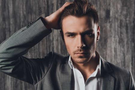 Foto de Attractive sexy man in business suit on the grey background - Imagen libre de derechos