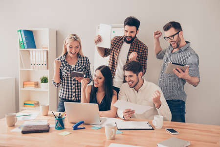 Photo for happy young workers  raised hands and looking at laptop - Royalty Free Image