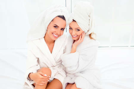 Photo pour Portrait of two happy smiling girls in bathrobes and turbans - image libre de droit