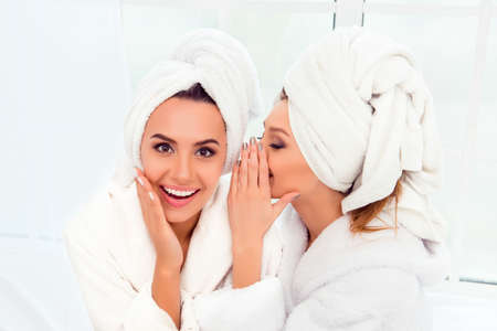 Photo pour Girl in bathrobe and  towel on her head telling secret to her sister - image libre de droit