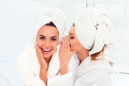 Foto de Girl in bathrobe and  towel on her head telling secret to her sister - Imagen libre de derechos