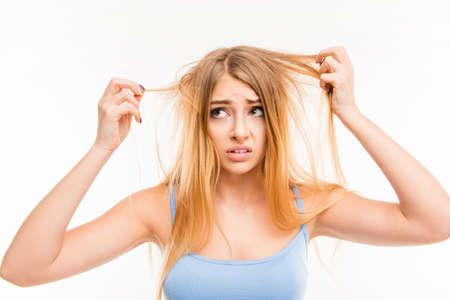 Foto de Sad girl looking at her dry hair - Imagen libre de derechos