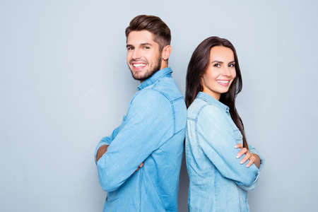 Photo for Cheerful hsppy man and woman with crossed hands standing back to back - Royalty Free Image
