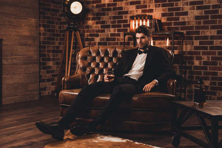 Photo pour Young man in suit resting on sofa with glass of brendy after working day - image libre de droit