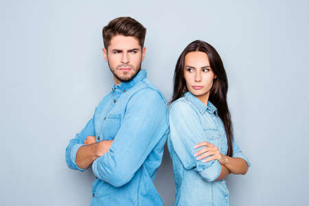 Photo for Serious man and woman with crossed hands standing back to back after quarrel - Royalty Free Image