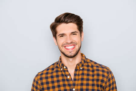 Photo pour Portrait of handsome young man with beaming smile on gray background - image libre de droit