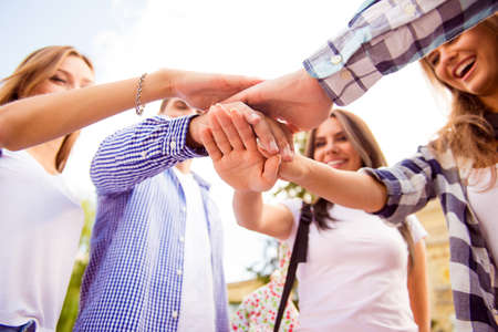 Foto de Close up photo of young friends putting their hands on top of each other - Imagen libre de derechos