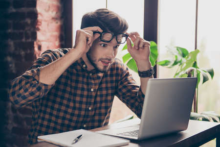 Foto de Unbeliveable! Young shocked surprised man in glasses looking on laptop - Imagen libre de derechos
