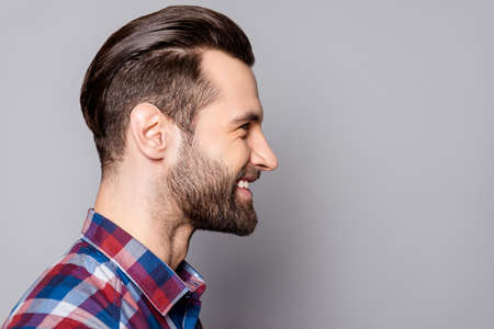 Photo pour A side view portrait of young handsome smiling man with stylish haircut standing against gray background - image libre de droit