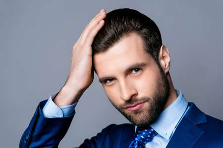 Photo for Close up portrait of serious handsome man in blue suit and tie touching his perfect hair - Royalty Free Image