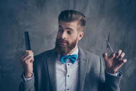 Foto de Portrait of Stylish young bearded man in a suit with bow-tie stands on a gray background and chooses between scissors and a comb. He solve going to the barbershop - Imagen libre de derechos