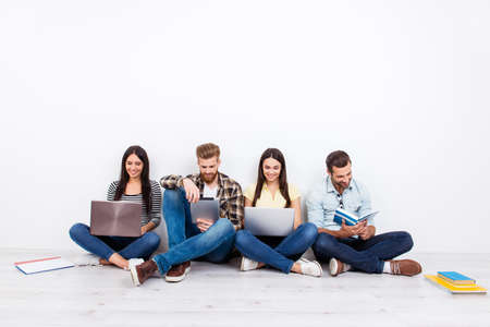Photo for Group of friendly smiling students sitting on the floor and using modern technology for studying - Royalty Free Image