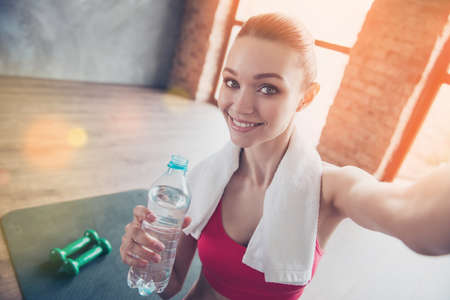 Foto de Close up portrait of beautiful cheerful girl in gym. She is making selfie with camera on her device, smiling and holding beverage - Imagen libre de derechos