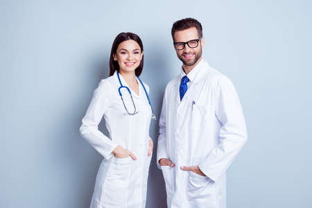 Foto de Two best smart professional smiling doctors workers in white coats holding their hands in pockets and together standing against gray background - Imagen libre de derechos