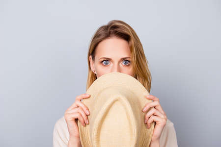 Photo for Close up portrait of cute young woman keeping silence and hiding her face behind hat - Royalty Free Image