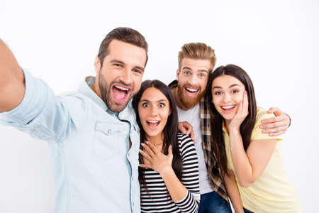 Foto de Group of excited friends making selfie on the camera of smartphone showing great emotions of amazement and excitement on white background in casual clothes - Imagen libre de derechos