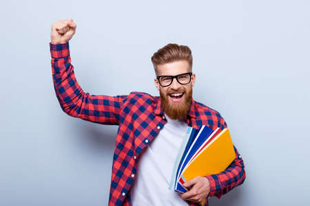 Photo pour Young cheerful student in glasses and in checkered shirt with books in hands celebrating ending of exams - image libre de droit
